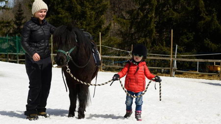 Photo of a kid leading a pony. A lovely winter activity for kids in Megeve